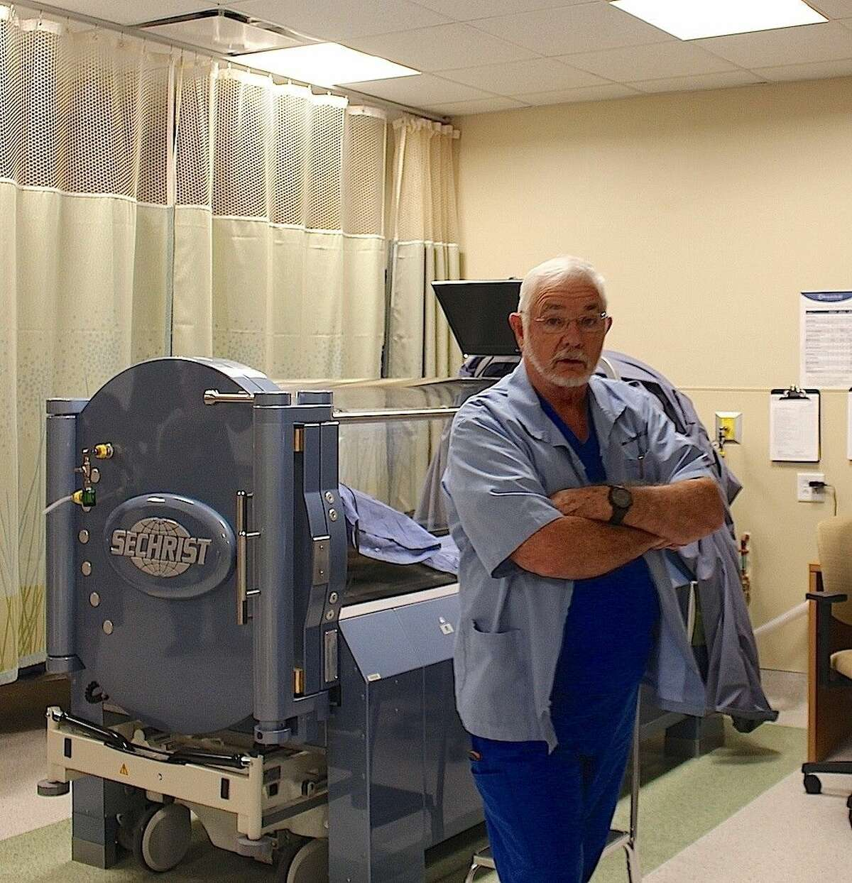 Wound Care Medical Director Dr. Donald Sprague stands in front of one of two hyperbaric chambers on campus.