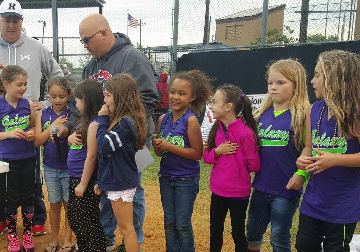 Peri Danaher, granddaughter of Bob Danaher and daughter of Kelly Danaher, recites the pledge of allegiance with her teammates at IT May Park during the 2016 Huffman Little League Opening Ceremonies Friday, April 1, 2016.