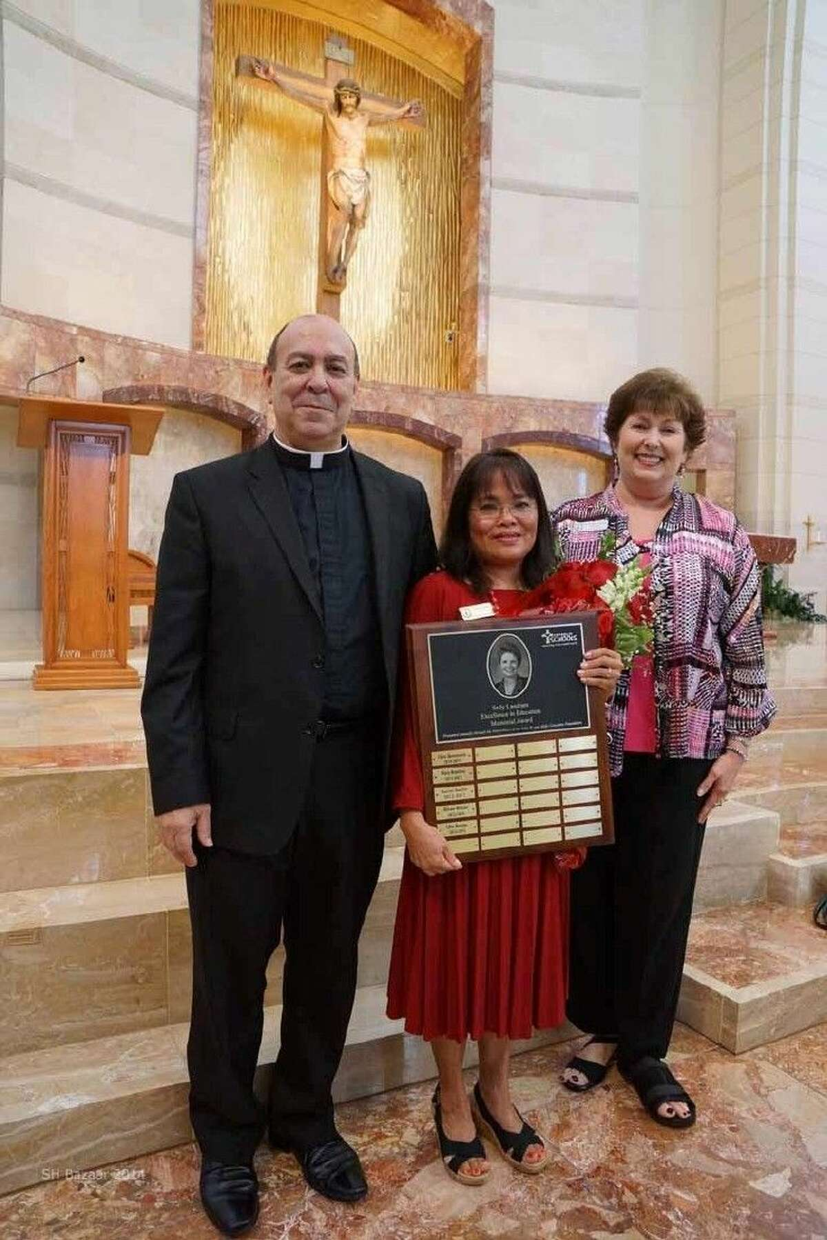The 2014-15 Sally Landrum Excellence in Teaching award was recently presented to Mrs. Lilia Keister, one of the founding teachers of St Helen Catholic School. Pictured from left: Fr. James Courville, Parochial Vicar, St. Helen Catholic Church; Lilia Keister, award winner; Phyliss Coleman, Principal, St. Helen Catholic School