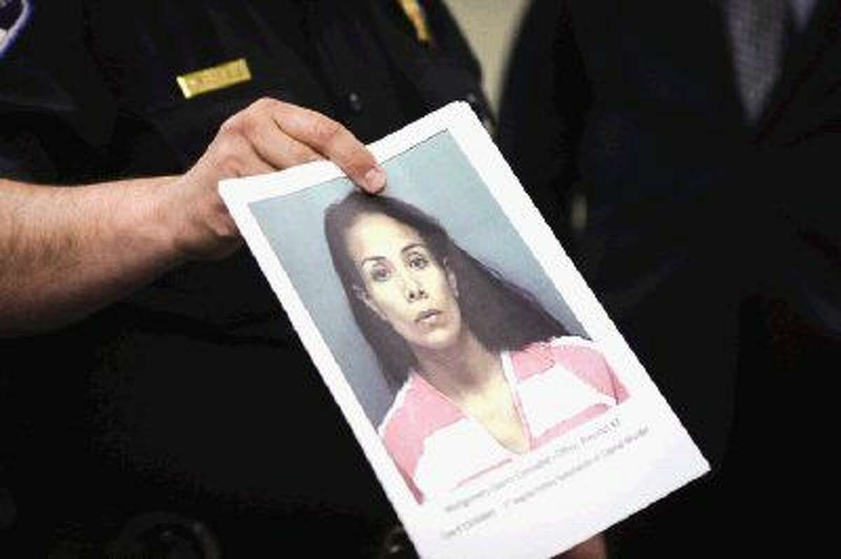 Matt Rodrigue, Chief Deputy Pct. 3 Constables Office, hands out an image of Maria Sosa to media during a press conference Friday. Sosa has been arrested for allegedly trying to hire someone to murder her husband.