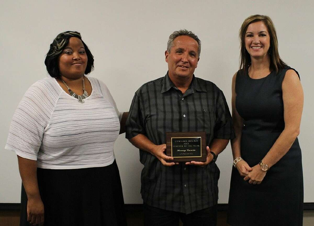 Upward Bound PE instructor Lenny Garcia, center is recognized as the Teacher of the Year by advisor Sharmeal Archie, left, and director Regan Metoyer.