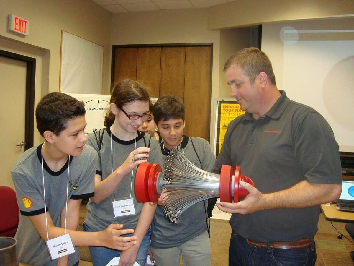 (right to left) James Lawrence, maintenance technician for Shell Pipeline Company LP, shows San Jacinto College EnergyVenture students, Isaiah Trevino, Sarah Faughtenbery, and Michael Garcia, a piece of equipment commonly referred to as a maintenance pig, which removes water, wax, and other buildup that may occur in a pipeline and keeps the flow of fuel moving efficiently through the pipe. Submitted photo