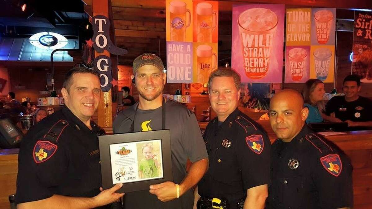 Law enforcement officers from the Harris County Precinct 4 Constable's Office presented Spring's Texas Roadhouse Managing Partner Shane Plaisance with a plaque thanking him for hosting Tip a Cop July 23, 2015.