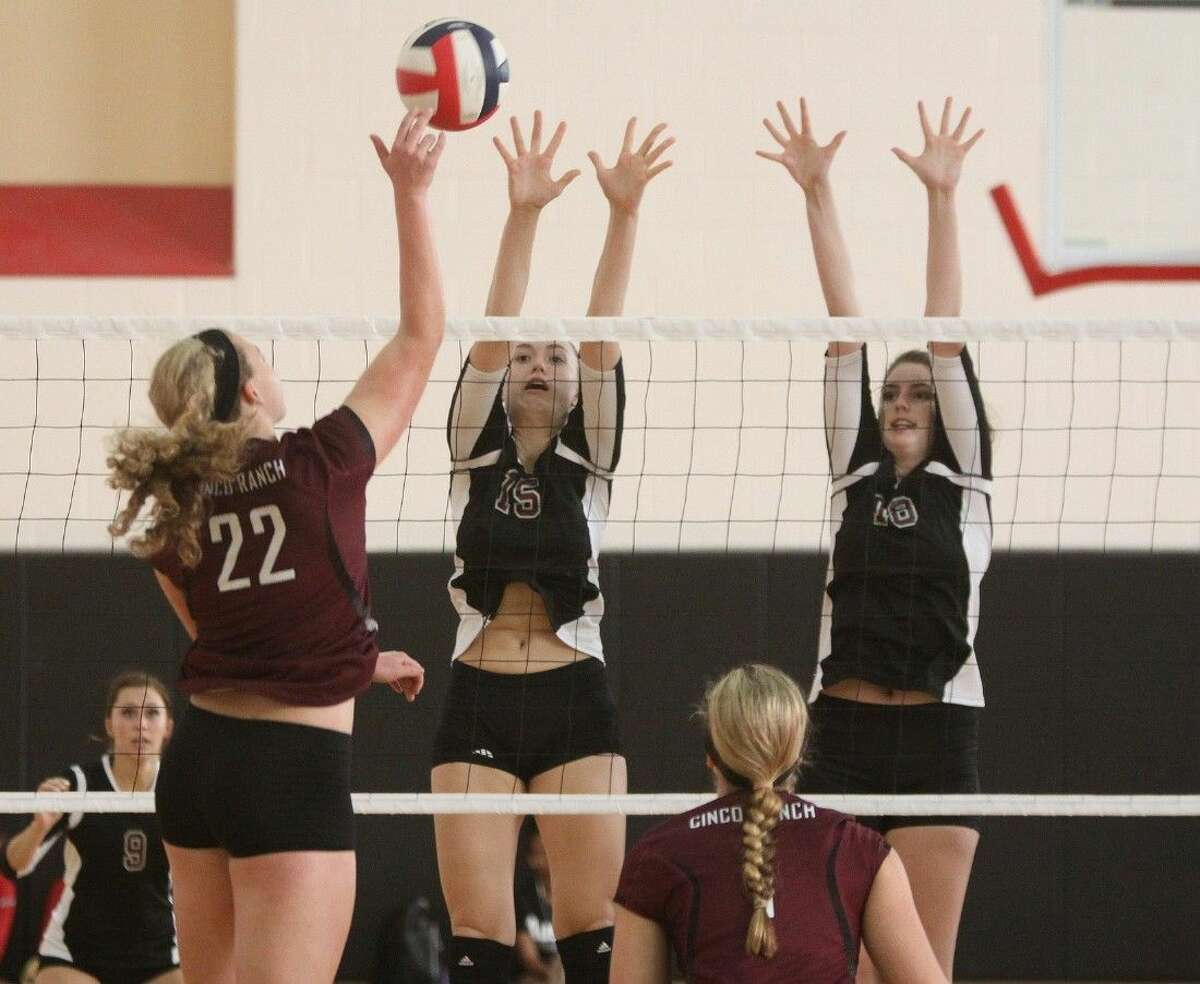 Cinco Ranch's Corin Evans spikes against Pearland's Cassidy Nussman and Sam Costello during the Spring Branch ISD volleyball tournament Thursday at Memorial High School in Houston,.