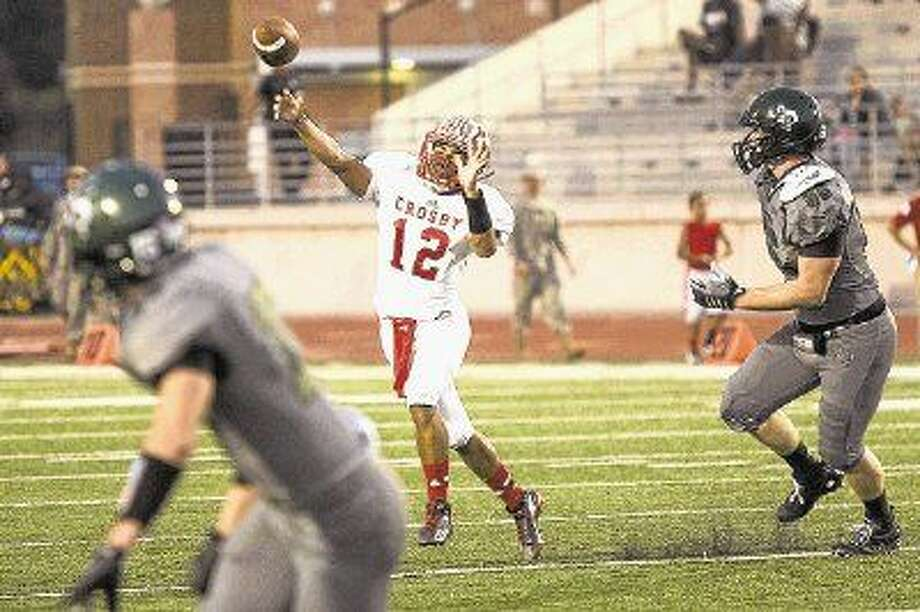 Cougars quarterback Tristen Cotton (12) passes on the run during Crosby's matchup against Kingwood on Oct. 2, 2014, at Turner Stadium. Photo: ANDREW BUCKLEY