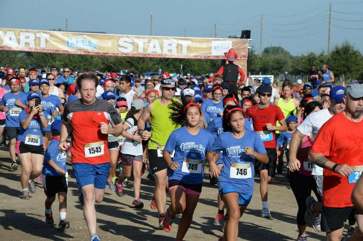 Runners take off at the gun at the start of Saturday's Corner Store Country Run at the Great Southwest Equestrian Center. Hundreds of residents came out to support the fundraiser for Big Brothers Big Sisters of America.