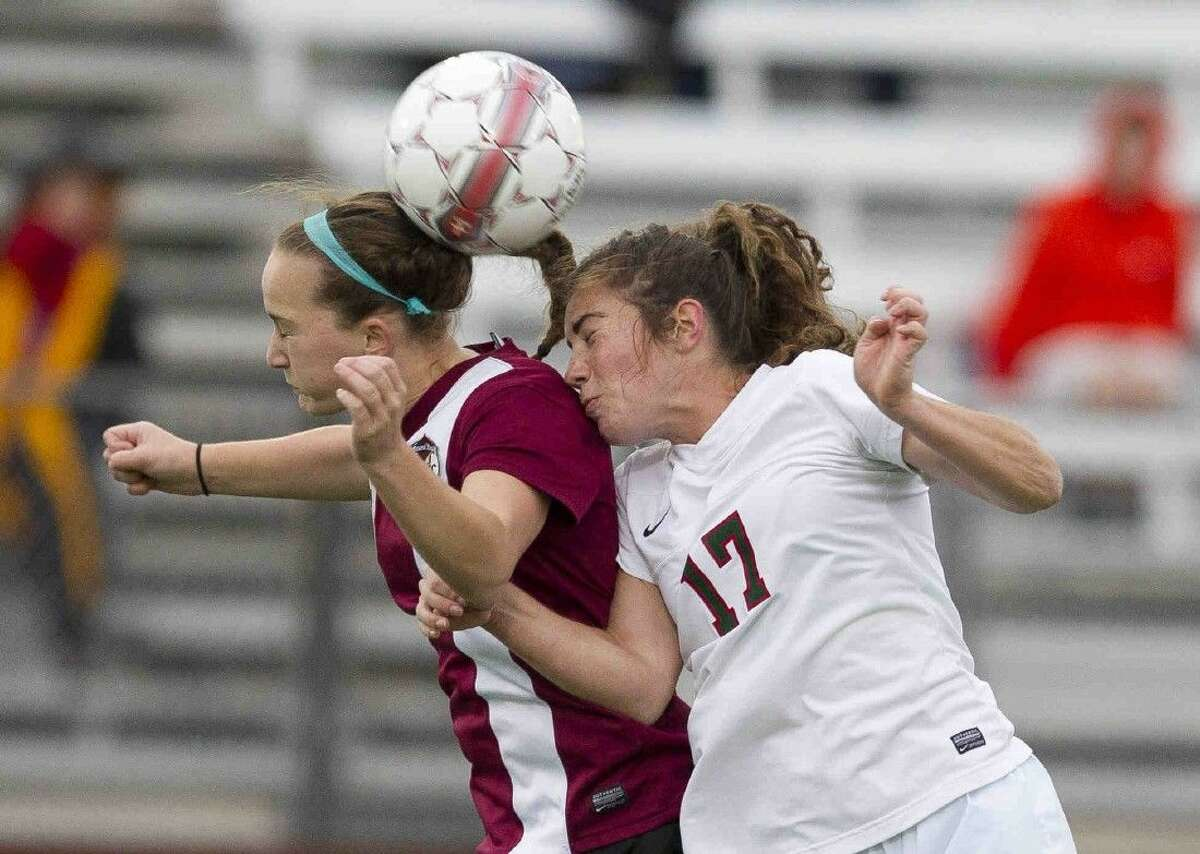 Round Rock's Nicki Springer heads the ball over The Woodlands midfielder Mollie Bond during the first period of a Region II-6A area round playoff game at A&M Consolidated High School Friday in College Station. Go to HCNpics.com to purchase this photo and others like it.