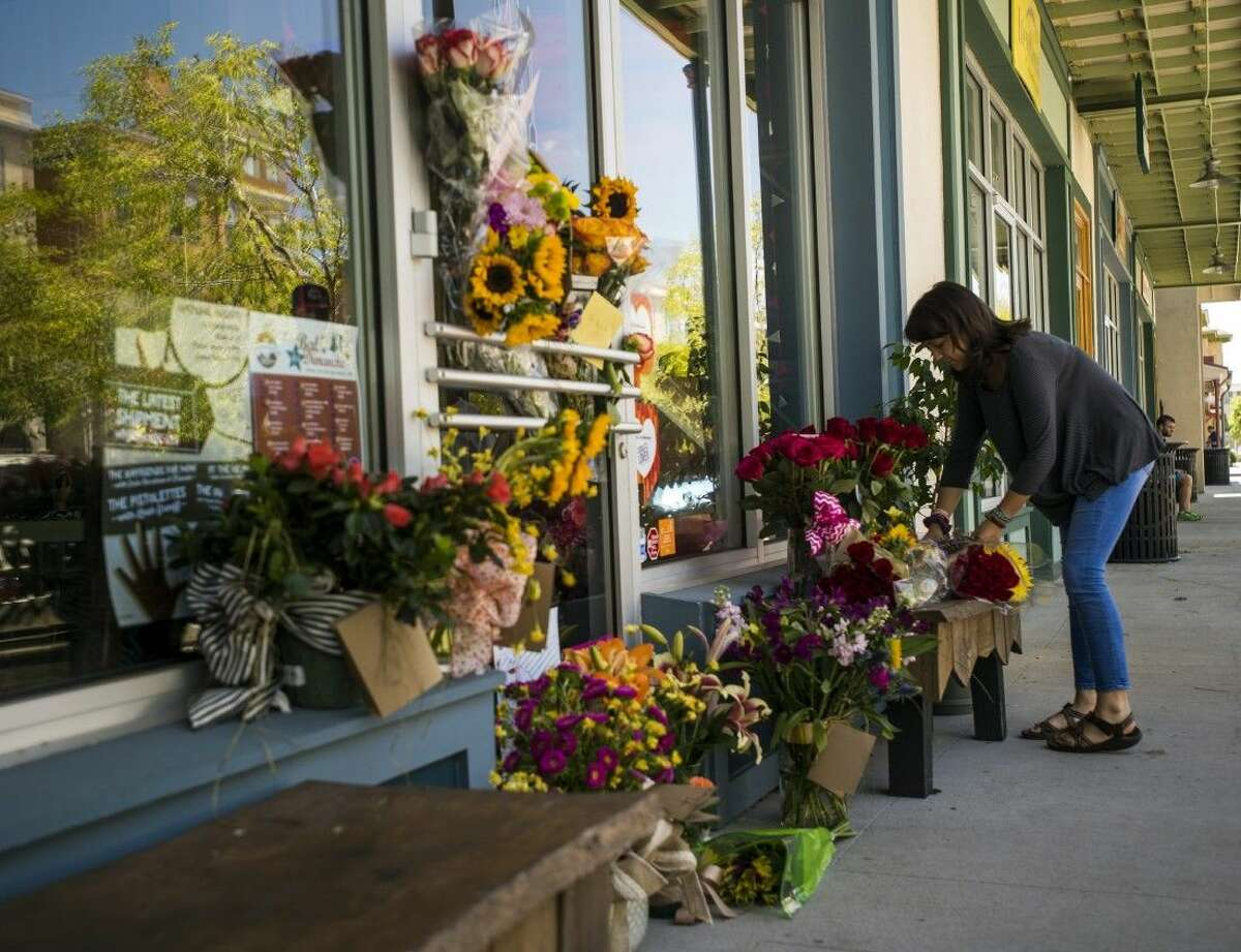 A woman leaves a bouquet of flowers at a makeshift memorial for store co-owner Jillian Johnson at Red Arrow Workshop in River Ranch in Lafayette, La., Friday.