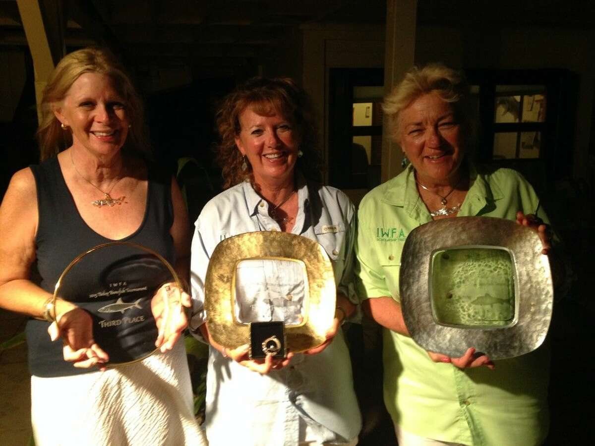 Connie O'Day (center) is shown with her first-place trophy at a national IIWFA fishing tournament in Belize.