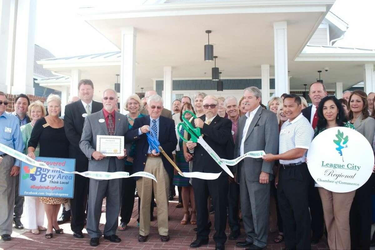 Senator Larry Taylor, front right, stands with Methodist Retirement Communities Board Chair Rev. Jack Womack, front center, and The Crossings Board Chair Tom Wussow, front left, as they cut the ribbon during a dedication of The Crossings community for active older adults Thursday, April 7.