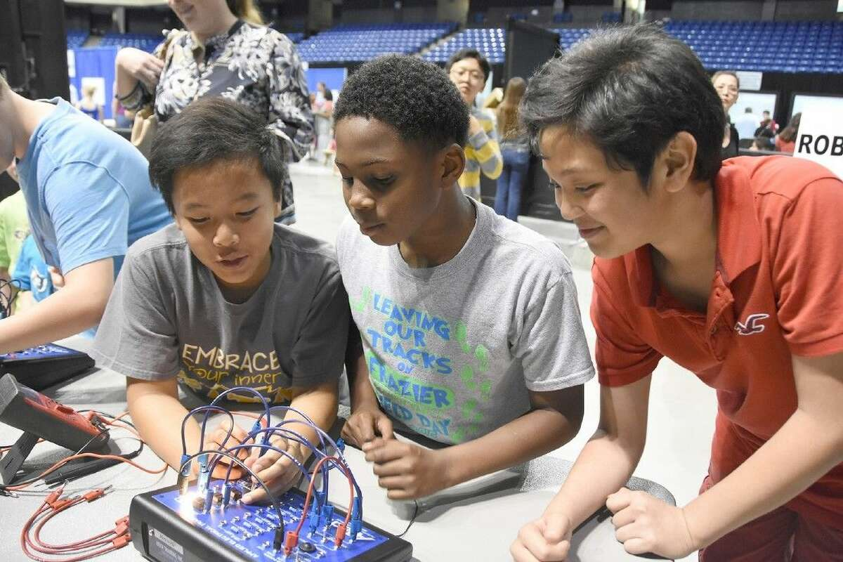 Frazier Elementary School students, from left, Tam To, Edward Ford and Larry Tran experiment with an electrical board showcased by the career and technical education department at the Technology Festival.