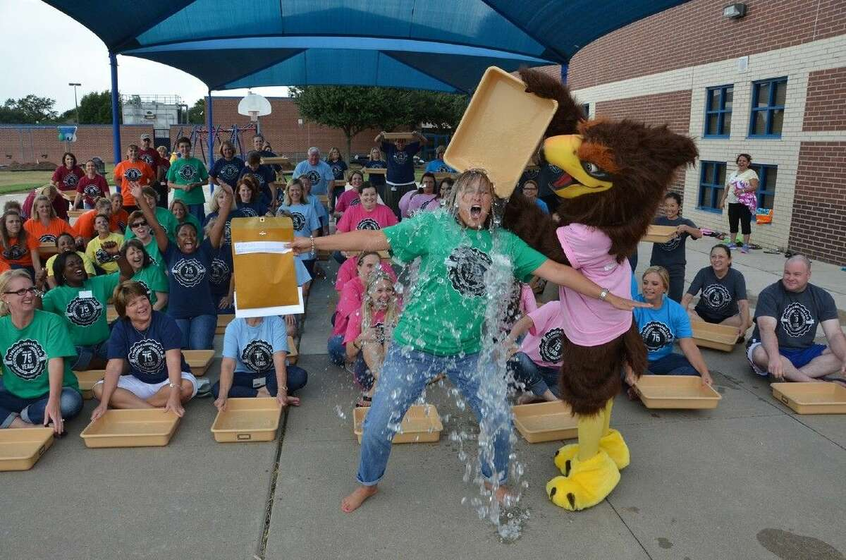 Farney Elementary School principal Tricia Reilly accepts the ALS Ice Bucket Challenge as the Farney Falcon pours the ice over her head. The entire Farney staff then responded by taking the challenge.