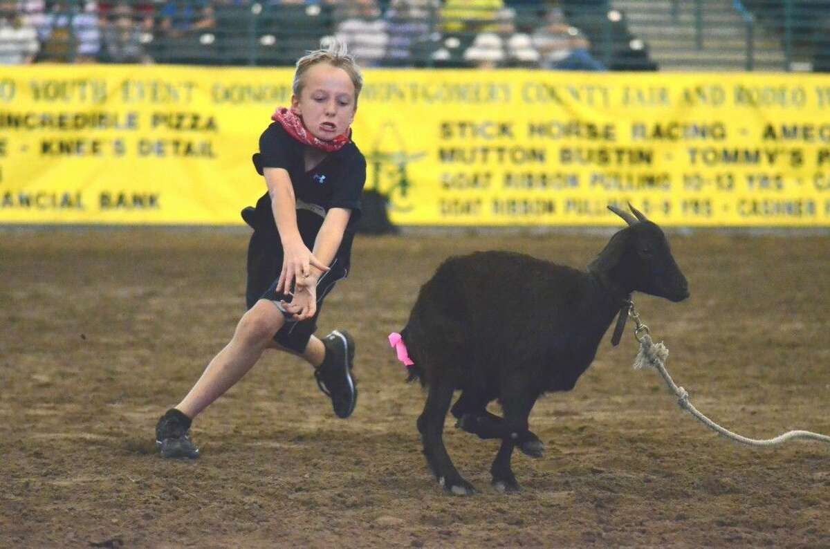 A boy runs for a goat in the ribbon pulling event Friday at the Montgomery County Fair Youth Rodeo.