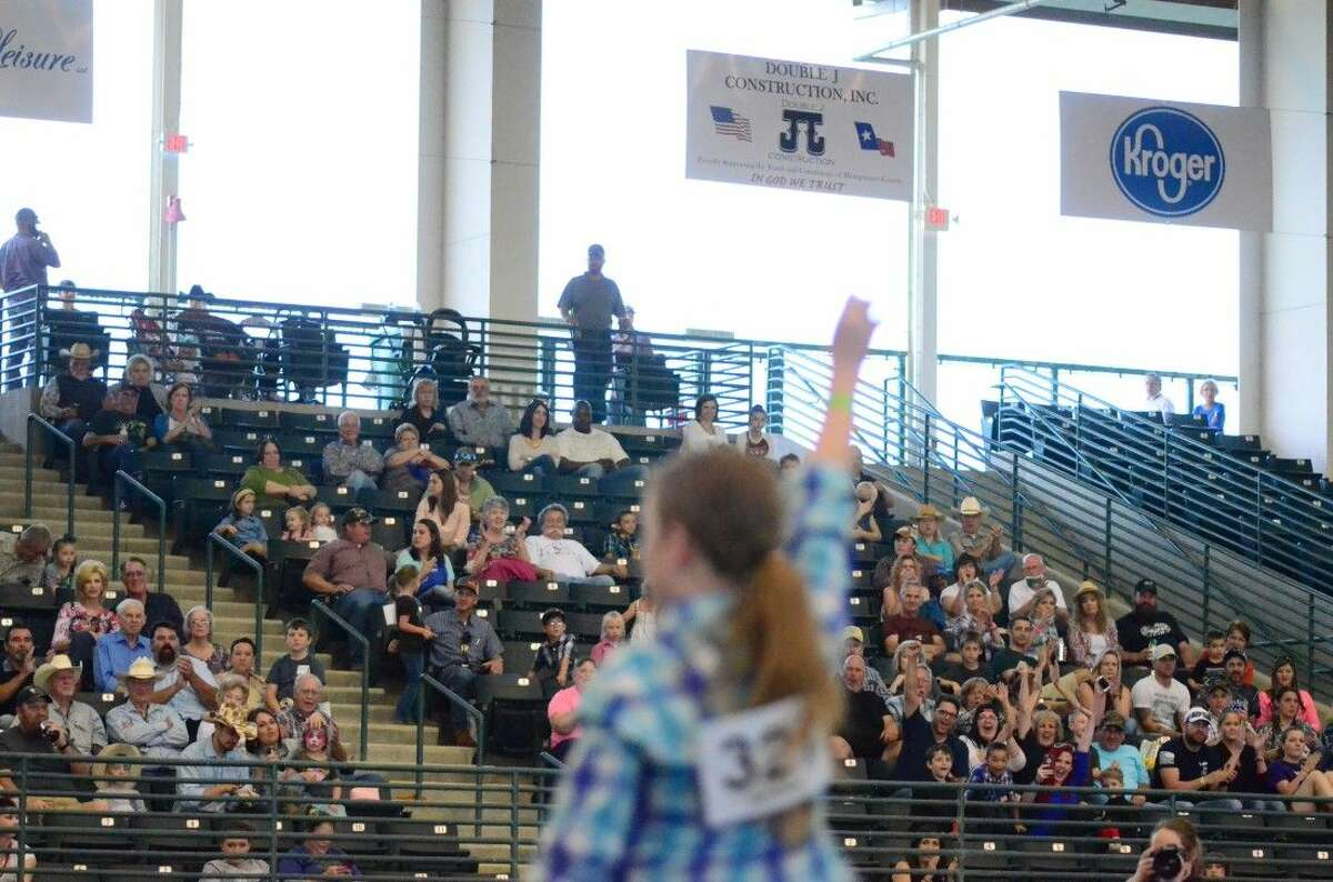 A crowd cheers on a girl who just competed in the goat ribbon pulling event Friday at the Montgomery County Fair Youth Rodeo.
