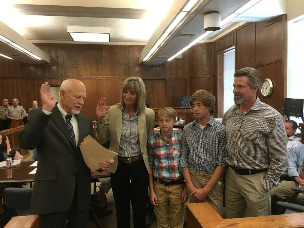Patty Maginnis was sworn in Friday next to her sons Eli Lovett, left, Luke Lovett, right, and husband Chris Lovett to fill the unexpired term of former Judge Mike Seiler who resigned from the bench in February.