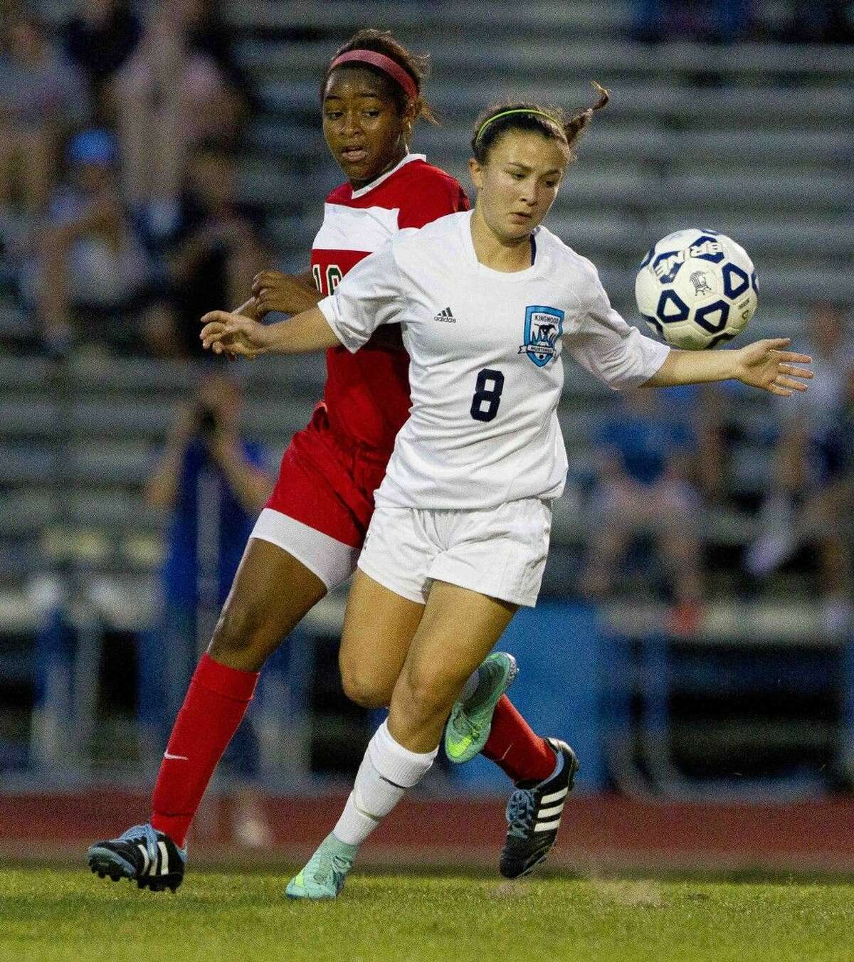 Kingwood's Catherine Childs looks to control the ball as The Woodlands forward Jazzy Richards chases her down during the first period of a District 16-6A girls soccer game at Kingwood High School Friday. The Woodlands defeated Kingwood 3-0. Go to HCNpics.com to purchase this photo and others like it.