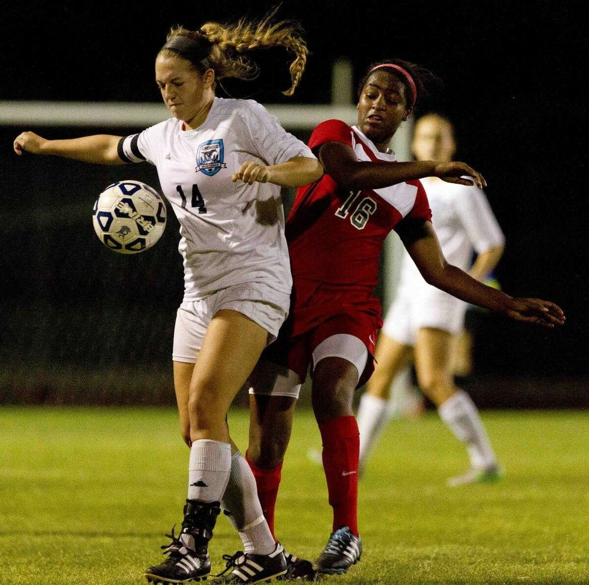 The Woodlands forward Jazzy Richards goes up against Kingwood's Angela Brady during the second period of a District 16-6A girls soccer game at Kingwood High School Friday. The Woodlands defeated Kingwood 3-0. Go to HCNpics.com to purchase this photo and others like it.