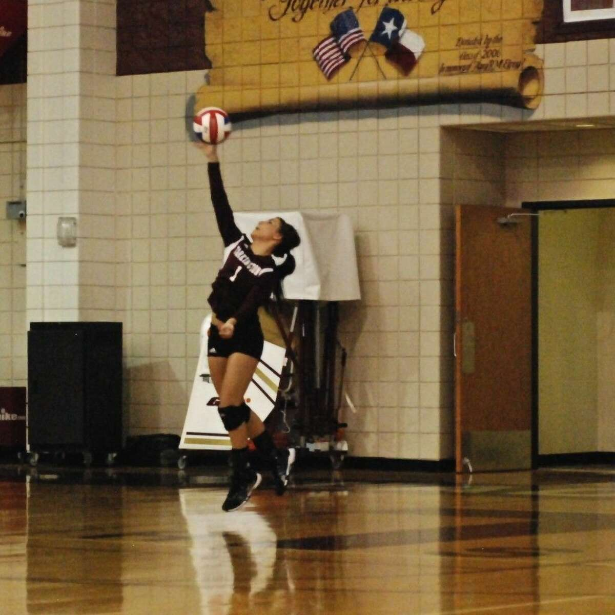 Paige Montgomery, back on the court for her senior year as defensive specialist for Tarkington's LadyHorns, serves in the first set against visiting Baytown Sterling, Aug. 22.