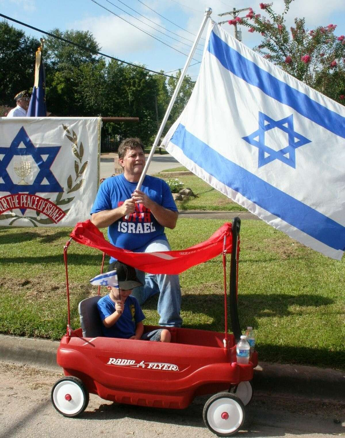 Spectators at the Aug. 23 march to support Israel, including young Parker in a Radio Flyer wagon, carried flags and donned shirts in support of Israel.