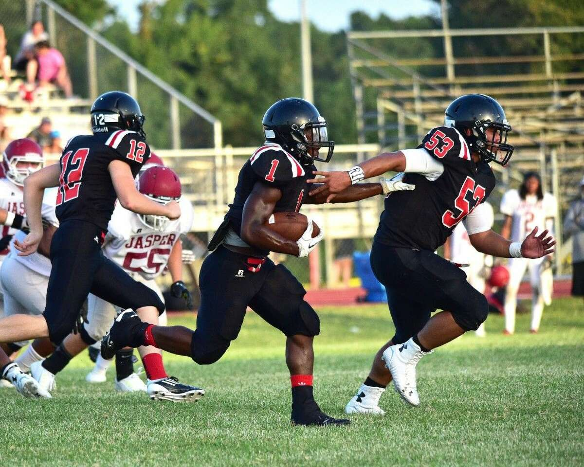 Drevion Cooper (1) races toward the end zone with Brock Barbay (12) and Rai Duenas (53) providing assistance.