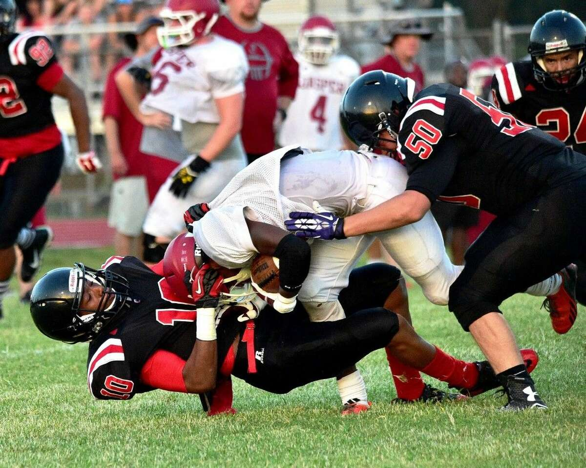 Deionta Harrison (10) pulls down one of the Jasper Bulldogs with assistance from Jeffery Stover (50).