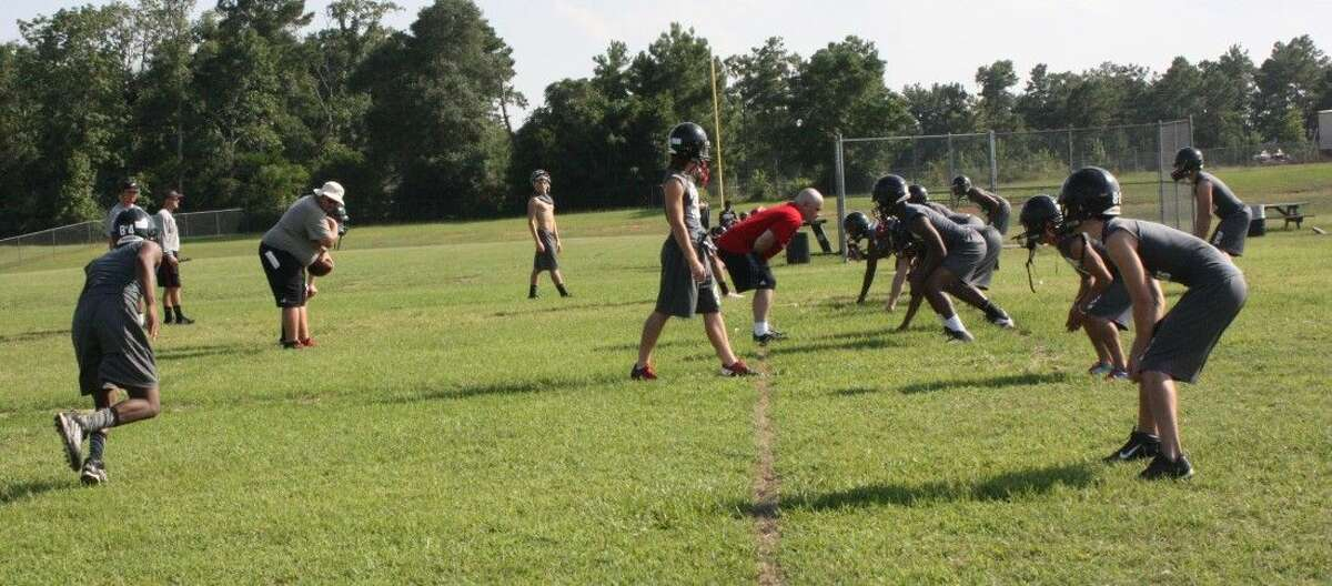 The Trojan varsity football team practices a blitz prior to their first scrimmage.