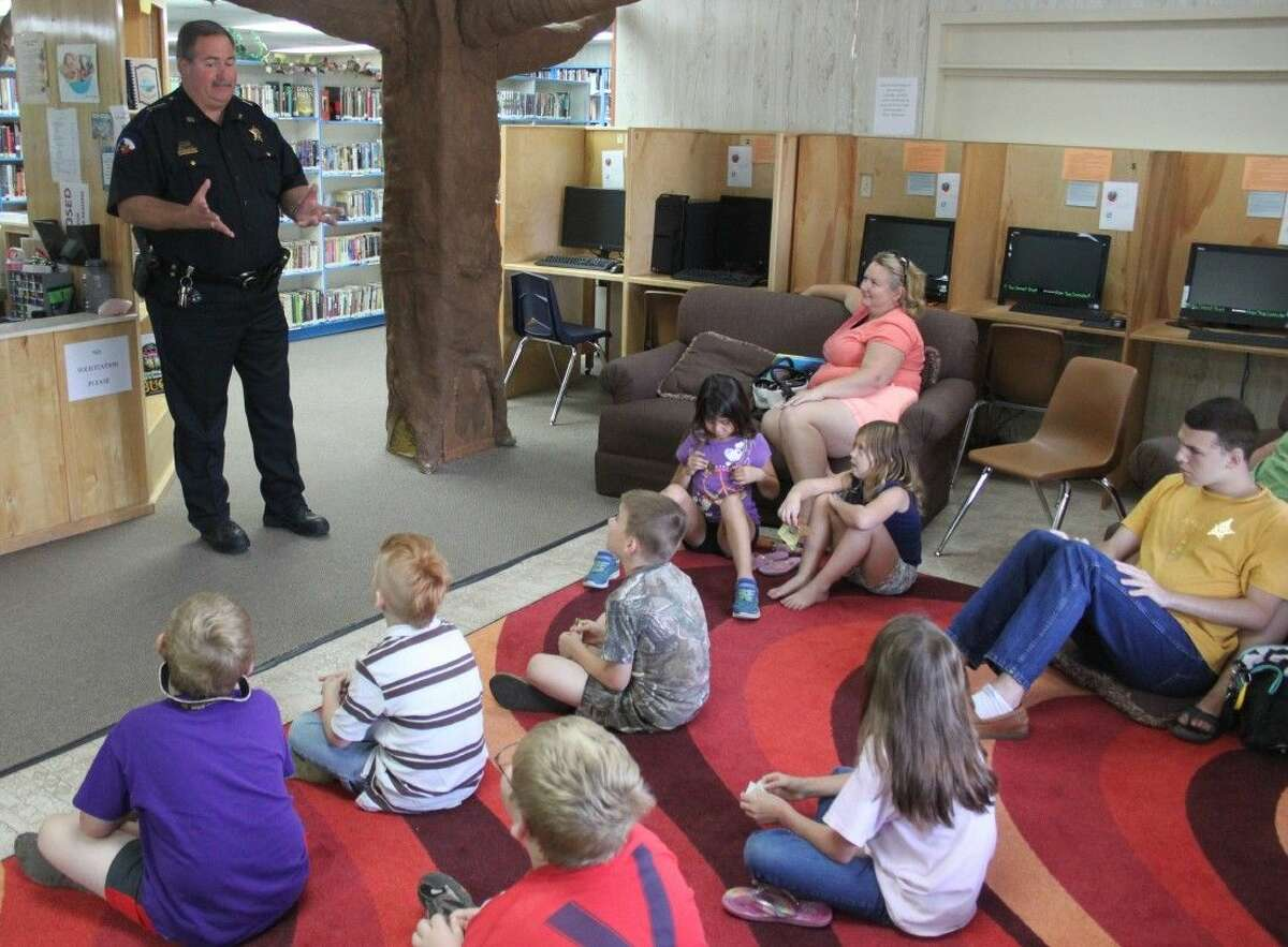 San Jacinto County Sheriff Greg Capers gives a group of children the perspective of being involved in law enforcement during Shepherd Public Library's Summer Reading program.