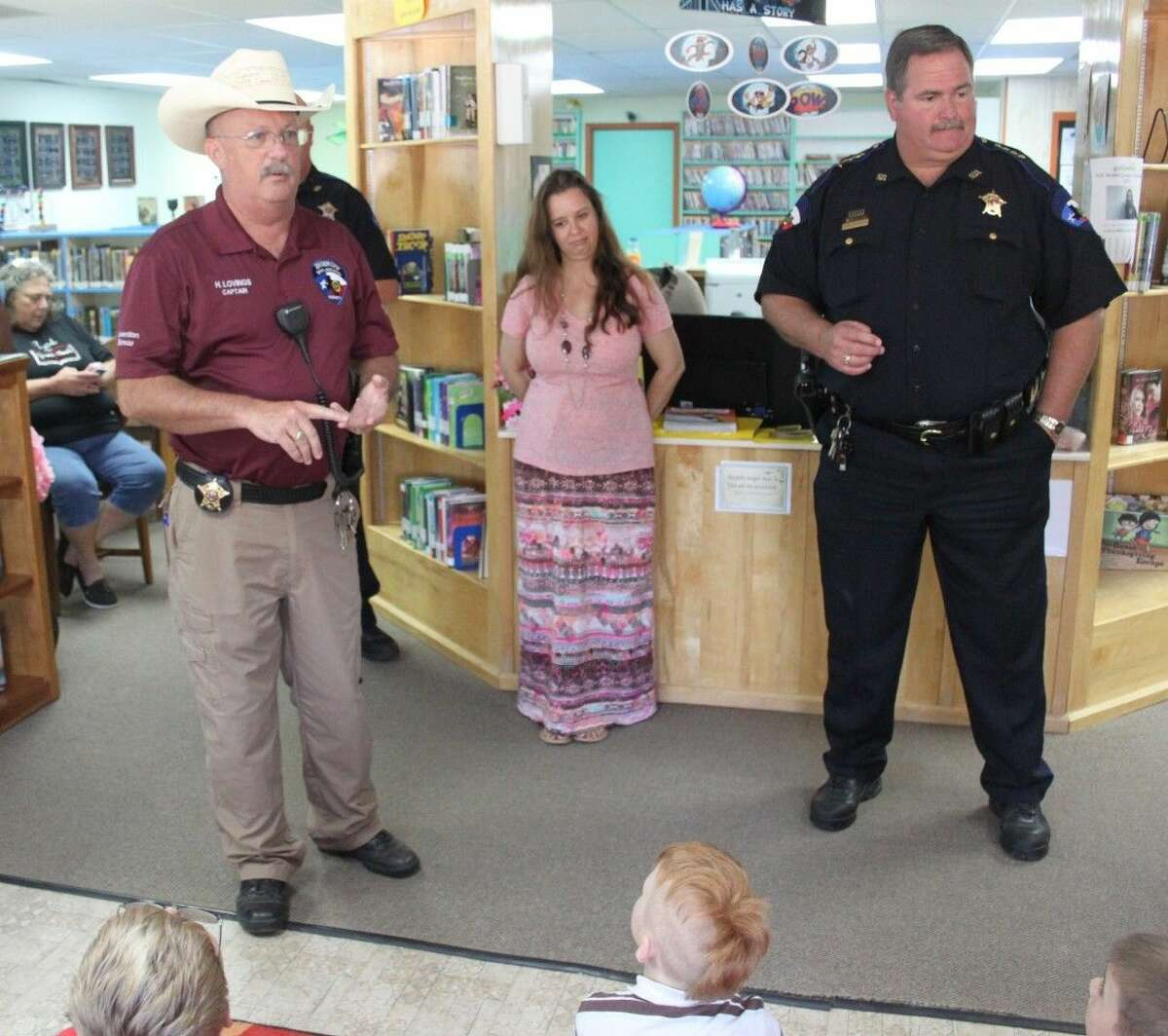 Captain Harley Lovings (left) tells the children gathered at Shepherd Public Library what it is like to be a jail captain as well as what it is like for a convict to be in jail.