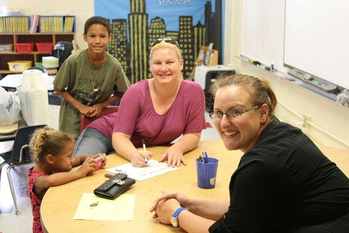 Kindergarten teacher Donna Flannery, front right, visits with Ashley Sheffield and her children Michael, age 8, and Mykala, 5, during Meet the Teacher Night on Thursday, Aug. 21, in Coldspring.