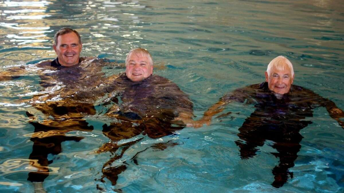 Not exactly wearing swim trunks, PISD Superintendent Kirk Lewis (middle) enjoys a dip in the school district's brand-new pool with board of trustees Jack Bailey to the left of Lewis and Marshall Kendrick.