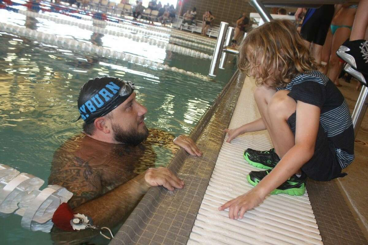 Donning the Sam Rayburn swim cap for the first time in nearly 20 years, Derrick Mauk talks to one of his twin sons as he awaits for the alumni swim meet to get under way, one of the festitivities during the new pool opening.