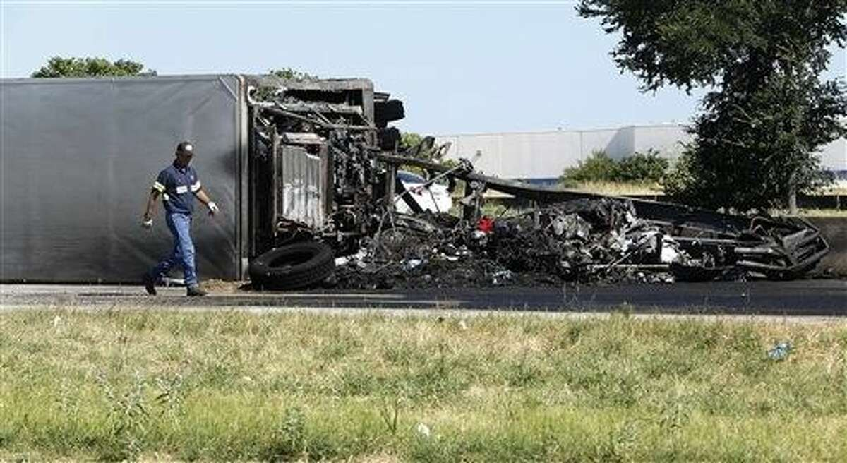 A man walks by the scene after a fiery crash on Highway 183 Sunday in Irving. Police say three Dallas-area firefighters have been hurt and a trucker killed when the 18-wheeler hit a stopped ladder truck at a DWI wreck scene.