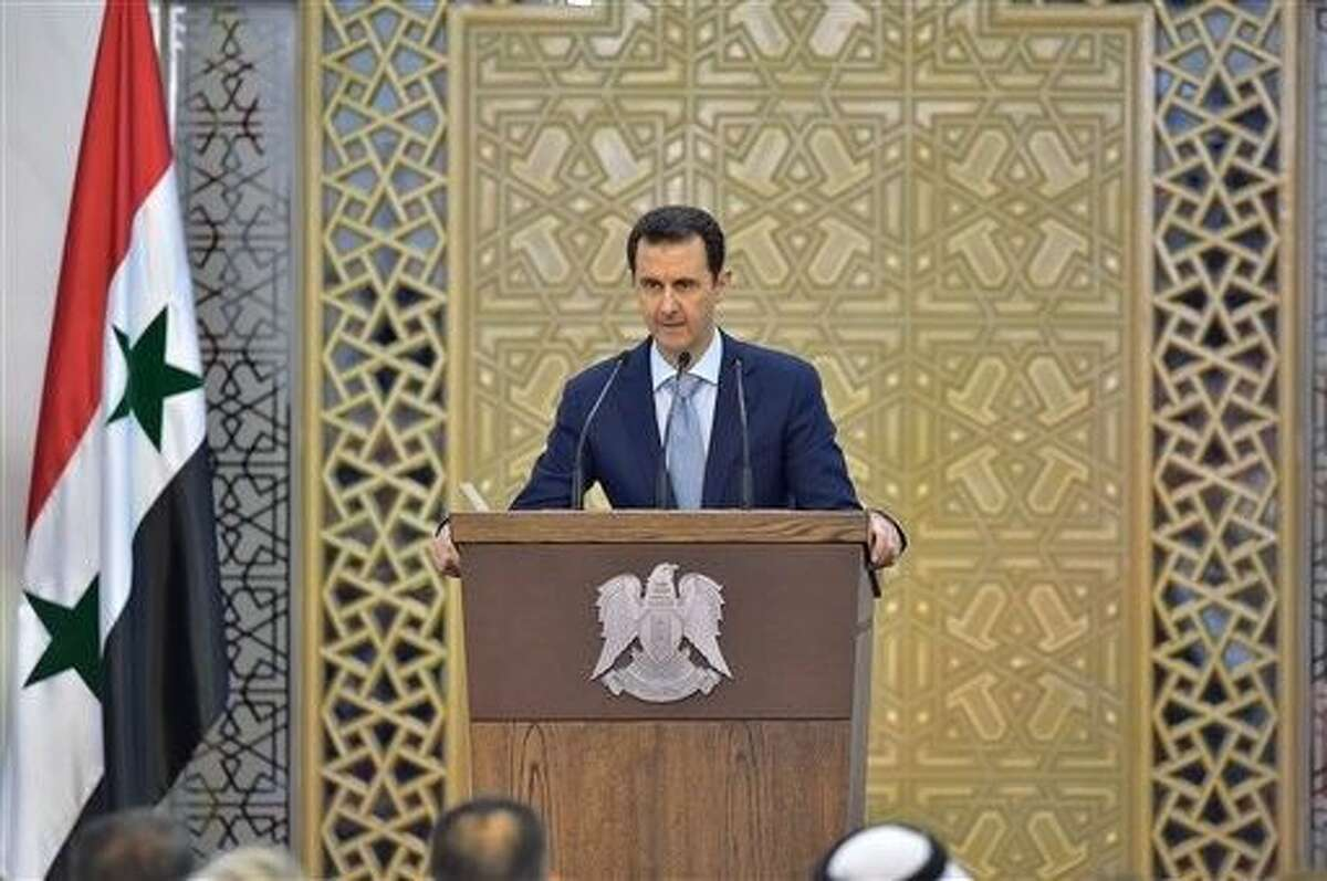 In this photo released by the Syrian official news agency SANA, Syrian President Bashar Assad delivers a speech in Damascus, Syria, Sunday.