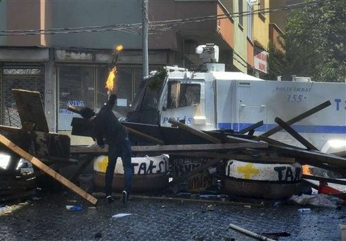 A left-wing protester hurls a petrol bomb towards a police car, behind a makeshift barricade background, In Istanbul, Sunday during clashes between police and people protesting against Turkey's operation against Kurdish militants.