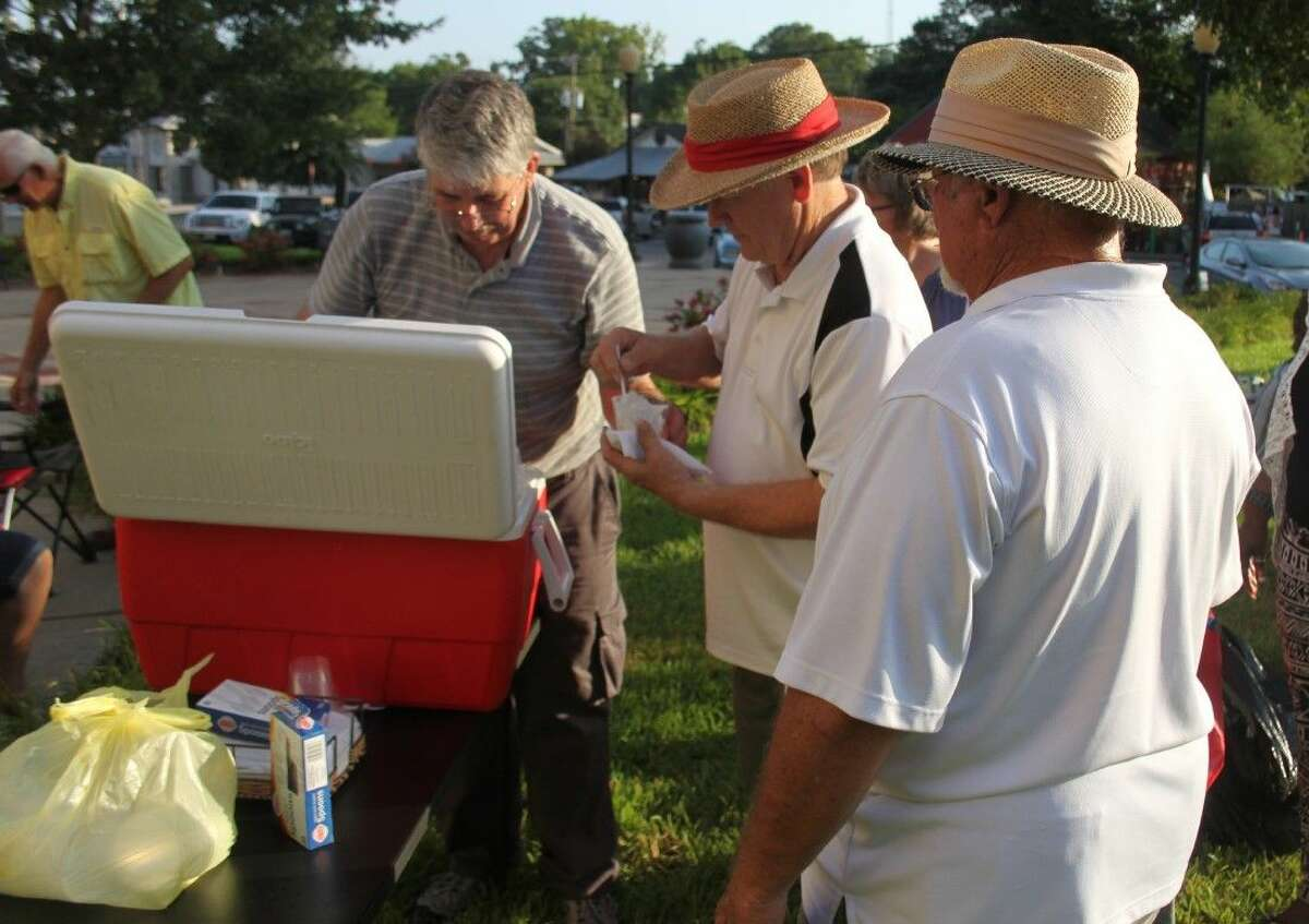 John Davis (left) serves ice cream to two attendees at the Summer Social.