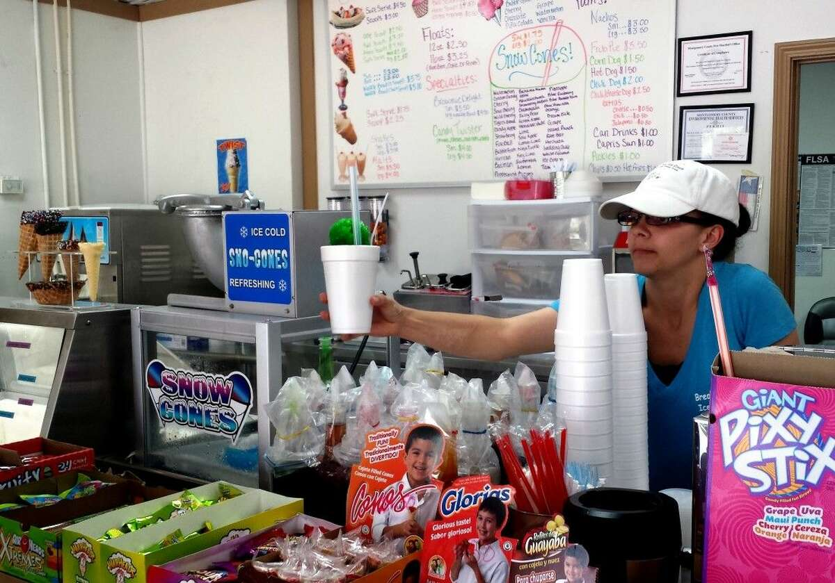 Break Time Ice Cream employee Krystal Dufur serves a snow cone to a customer on Friday, July 24.