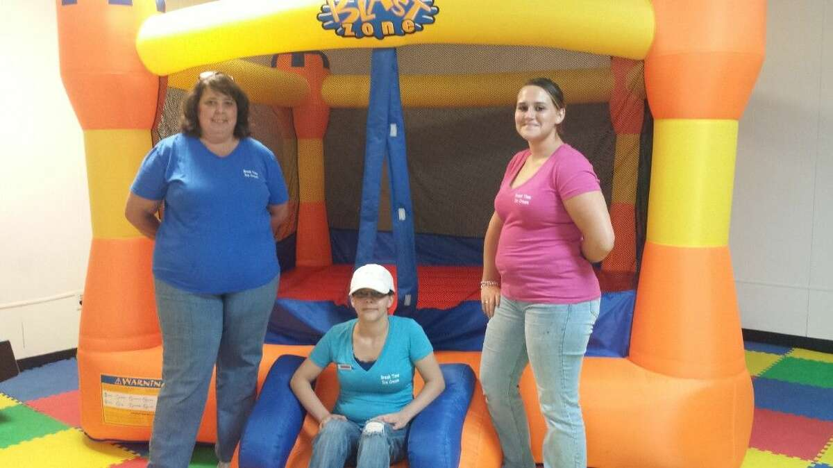 Break Time Ice Cream owner Lora Reis (left), pictured with employees Krystal Dufur and Cecelia McClellan, recently added a much bigger bounce house in the playroom, which is free for customers.