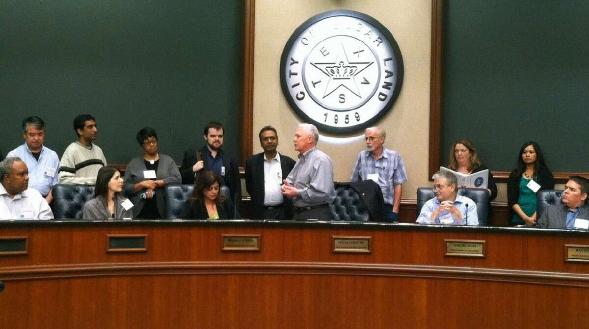 Mayor James Thompson (center) prepares Sugar Land 101 class members for their roles in a mock city council meeting.