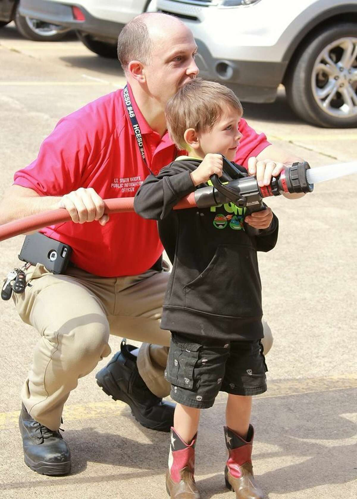 Lt. Simon VanDyk. shows a student how to work the hose at Golbow Elementarty's Health and Safety Fair April 2.