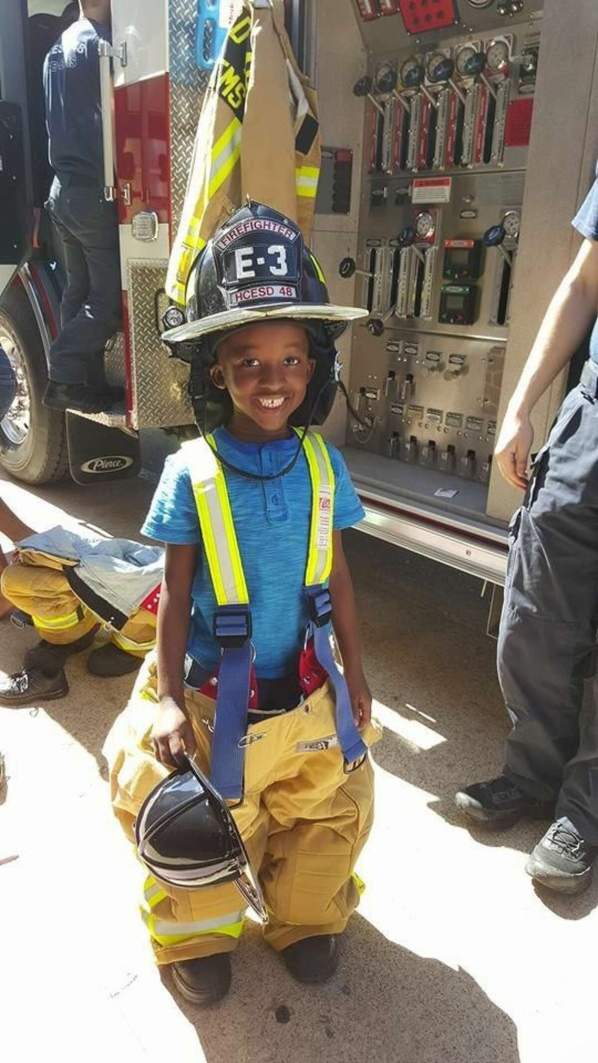 A young student beams as he tries on the bunker gear at Golbow Elementary's Health and Safety Fair. Students were allowed to tour the vehicles and try on equipment on Engine 3.