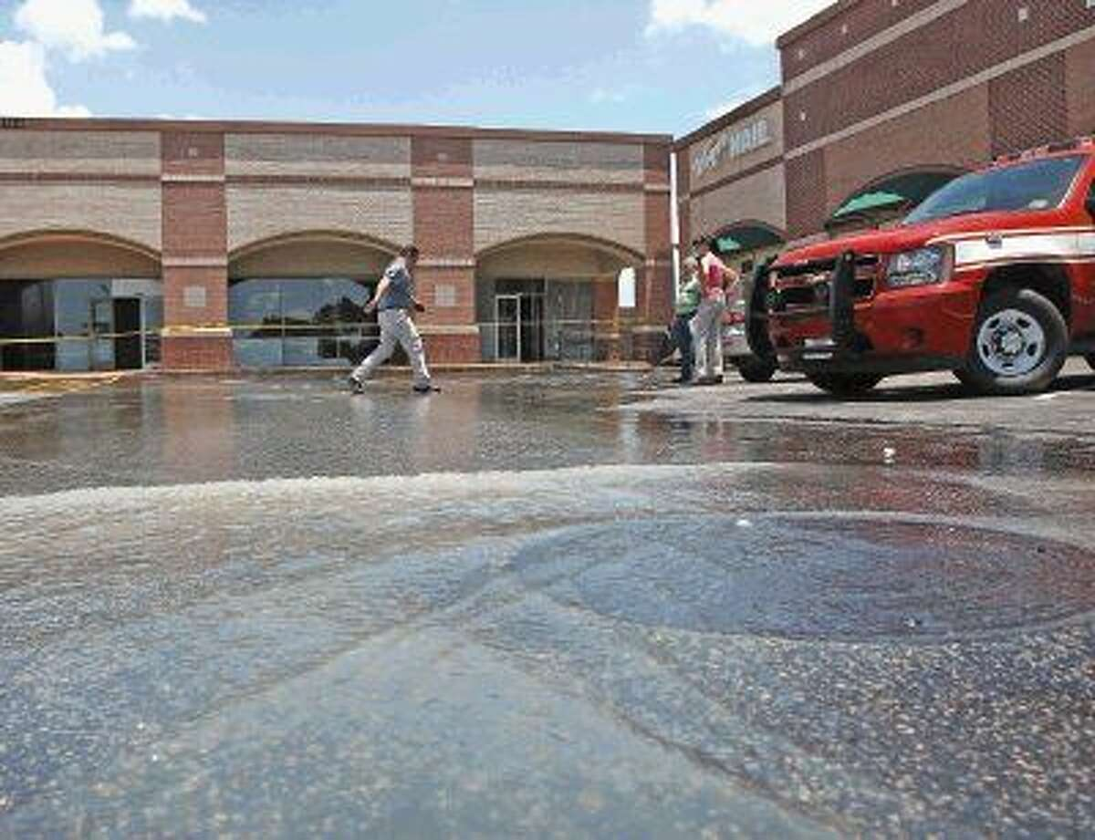A person steps lightly through the water as it pours out of the strip center next to HEB after a water line break.