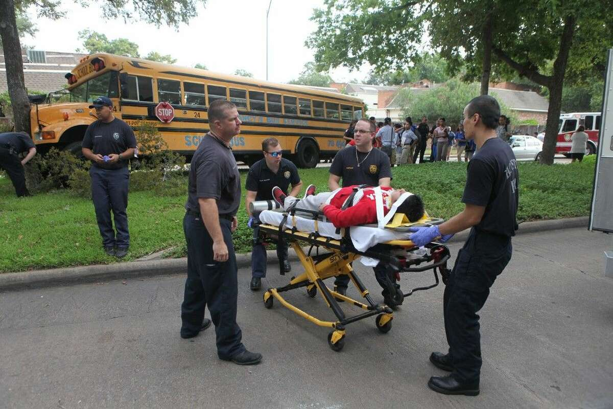 Houston Fire Department loads a middle school student into an ambulance at the scene of a school bus accident.