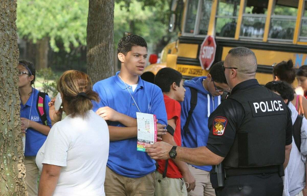 Middle school students talk with police at the scene.