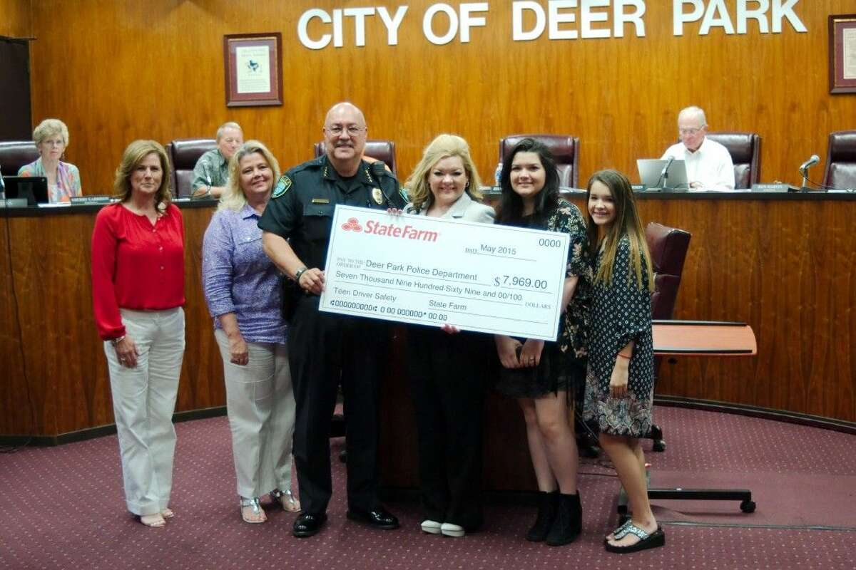 Representatives from Deer Park Chipper Holt State Farm Office, left, stand as Pasadena State Farm agent Dalinda Madrigal, presents Deer Park Chief of Police Gregory L. Grigg with a check for $7,969 to be used for teen driver safety training Tuesday, July 21.