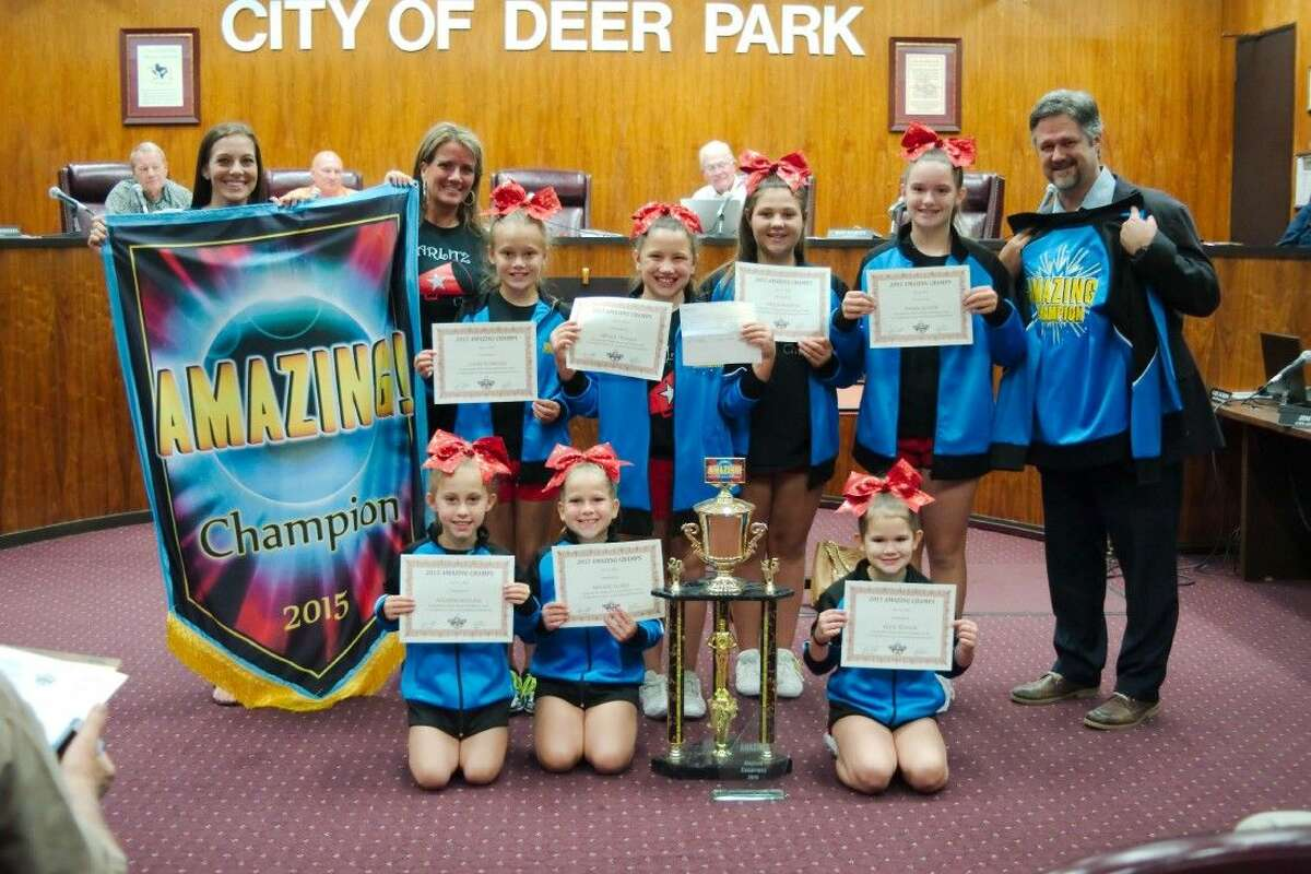 Members of the Deer Park Texas Starlitz cheer team are recognized by Deer Park Mayor Jerry Mouton, Jr., right, and the Deer Park City Council after the Starlitz took first place in the Amazing charity cheer competition in San Antonio and donated their $1,000 winnings to the Make a Wish Foundation Tuesday.
