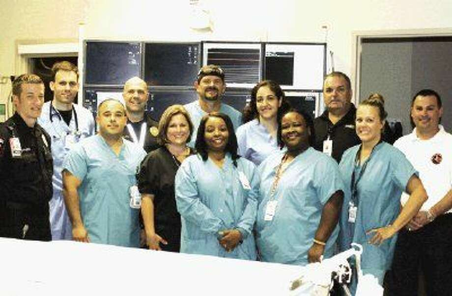 """Saving heart attack patients is a team effort by Memorial Hermann Northeast Hospital's Cardiac Catheterization Laboratory and Emergency Center staff and members of the Harris County Emergency Corps. Pictured from left to right are Monty Northern, Dr. Bret Weathers, Aaron Garcia, Chivas Guillote, Jennifer Braren, Jason Warshaw, Ursula Gilstrop, Dr. Armita Atashband, Glenda Benjamin, James """"Bubba"""" Campbell, Brittany Adam and Jeremy Hyde."""