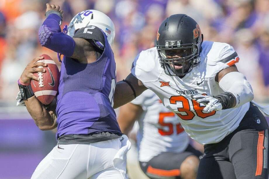 Bush graduate Emmanuel Ogbah, pictured playing against TCU, was voted Big 12 Defensive Lineman of the Year after 11 sacks and 17 tackles for loss as a sophomore. Photo: OSU Athletics
