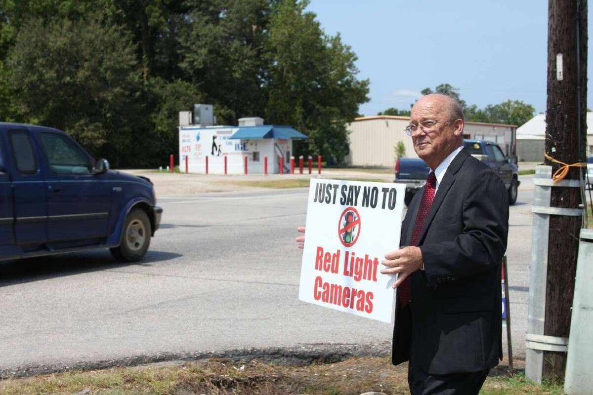 """Aubrey Vaughn holds up a sign reminding motorists to """"say no"""" to red light cameras in Cleveland, where voters rejected the devices.."""