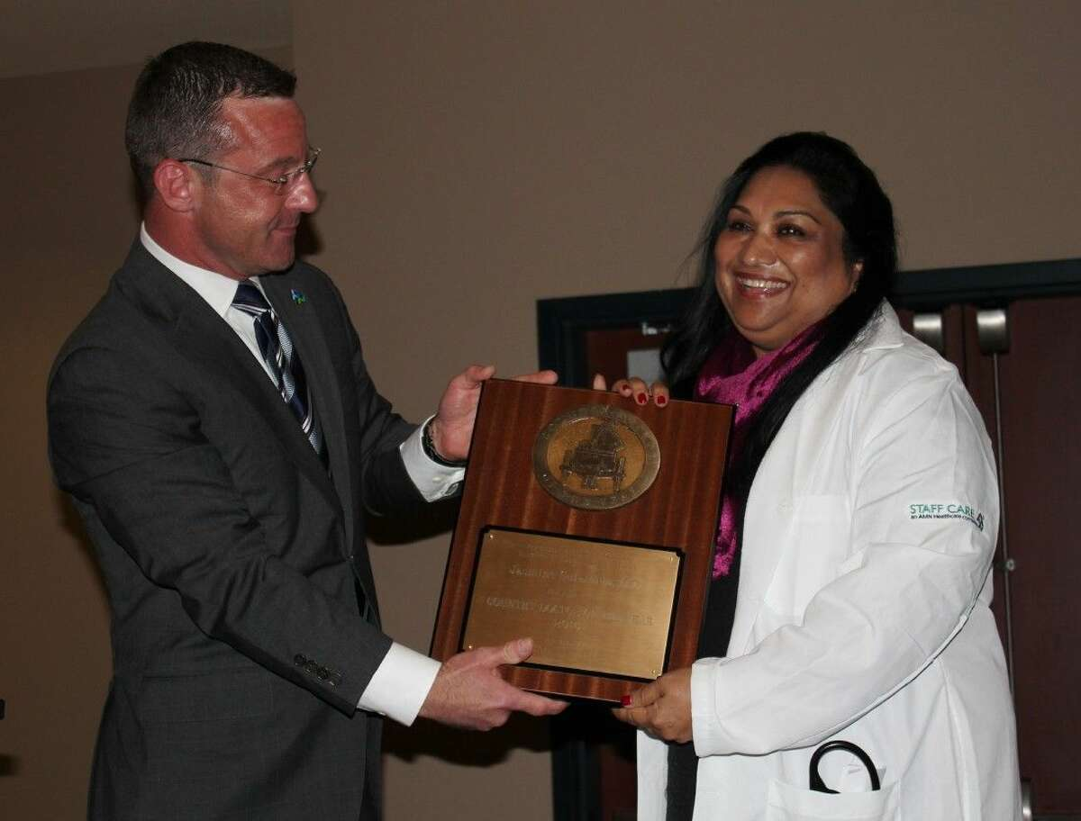 Dr. Jasmine Sulaiman accepts a plaque for being named 2016 Country Doctor of the Year from Sean Ebner, president of Staff Care. The presentation was made Friday, April 8, during a luncheon in Sulaiman's honor at the Cleveland Civic Center.
