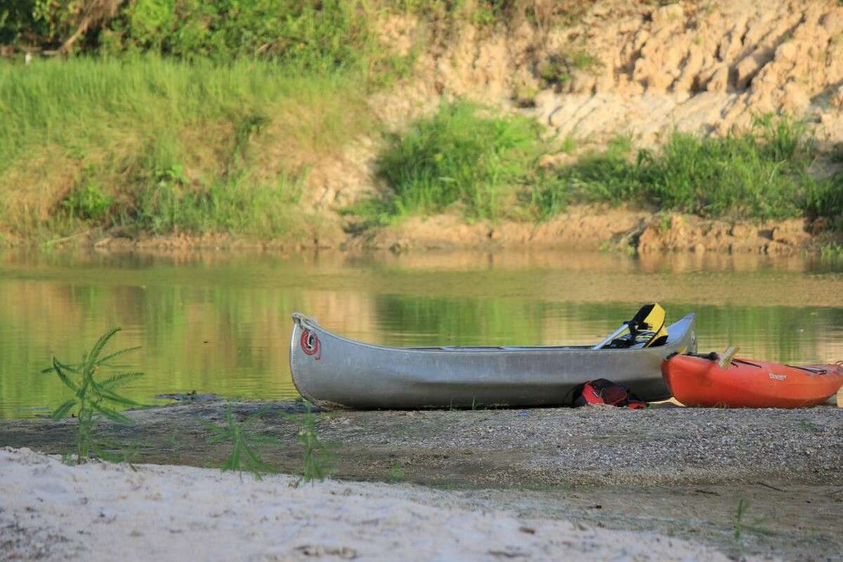 Staff photo by Minza KhanHarris County canoes sit near the creek while memebers take a break.